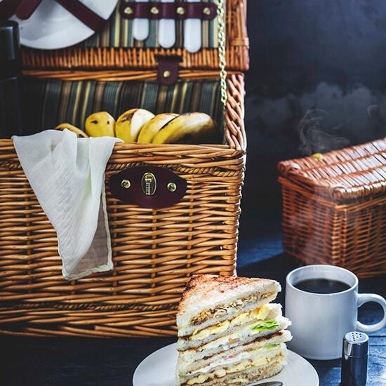 Panier en osier incluant une banane et un torchon et au premier plan un sandwish triangle dans une assiette et une tasse de café