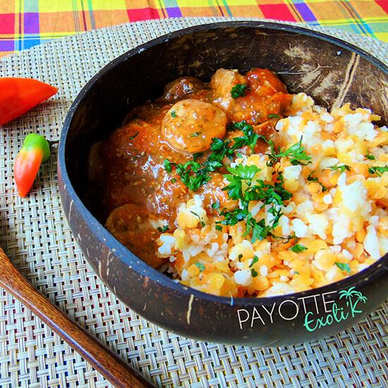 Assiette en bois présentant du rougail saucisse et du riz parfumé