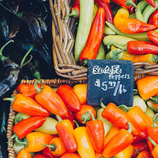 Etale de piments rouge avec une étiquette en ardoise indiquant le prix